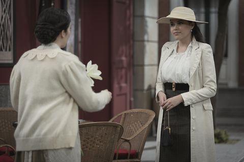 Human body, Hat, Headgear, Chair, Street fashion, Sun hat, Conversation, Blazer, Beige, Vintage clothing,
