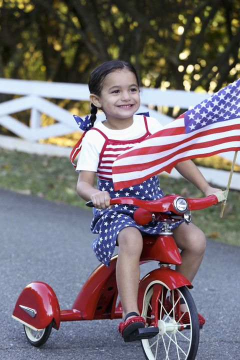 child riding patriotic bicycle with american flag