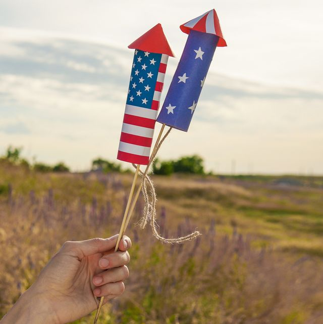 happy fourth of july woman or man hand holding fireworks rockets in national american colors over cloudy blue sky