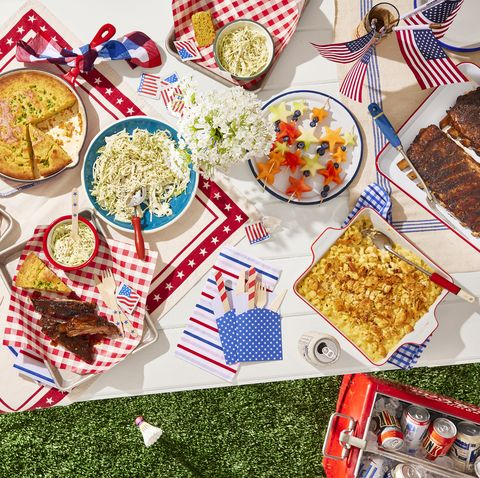 a table set with red white and blue for the fourth of july and filled with cornbread and ribs and slaw and fruit