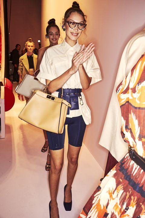 Fashion, Fashion model, Clothing, Fashion design, Yellow, Fashion show, Shoulder, Eyewear, Shorts, Runway,