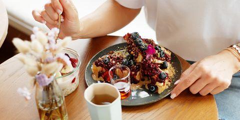 Girl eating healthy breakfast in cafe closeup