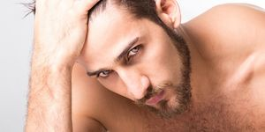 Close-Up Of Shirtless Handsome Man Against White Background