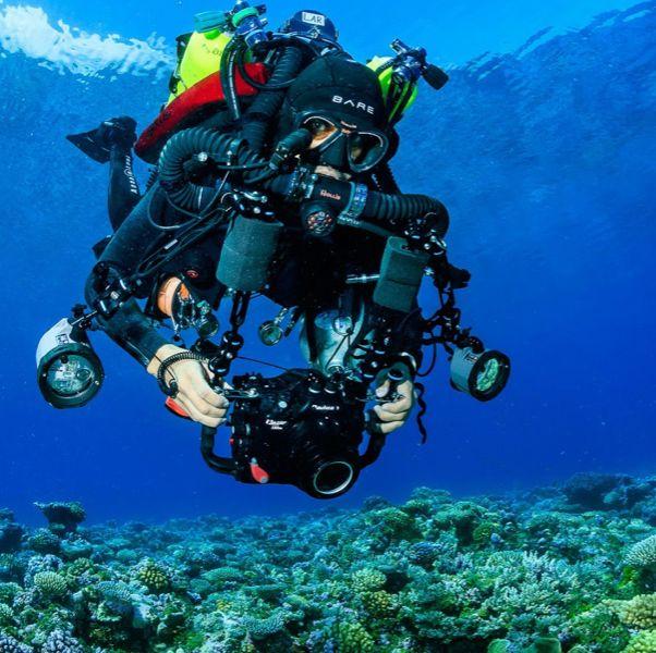 一個人穿著潛水裝在藍色的海裡
