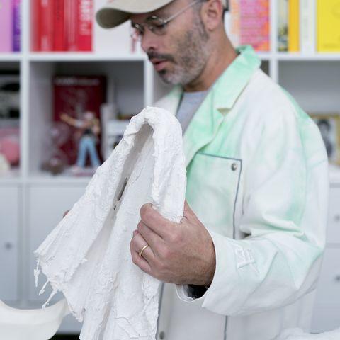 daniel arsham穿著白袍拿著白色時鐘