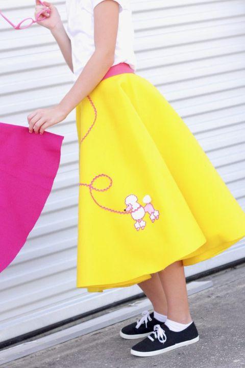 girl wearing yellow poodle skirt