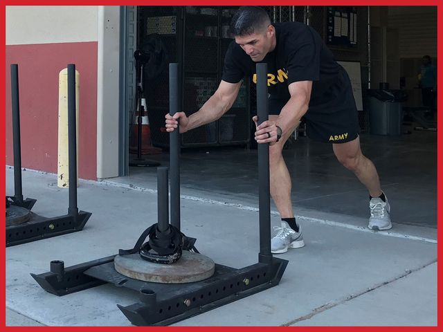 army major timothy cox pushing a weight sled