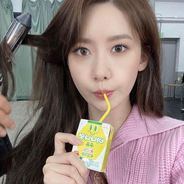 潤娥穿著粉色上衣在喝飲料