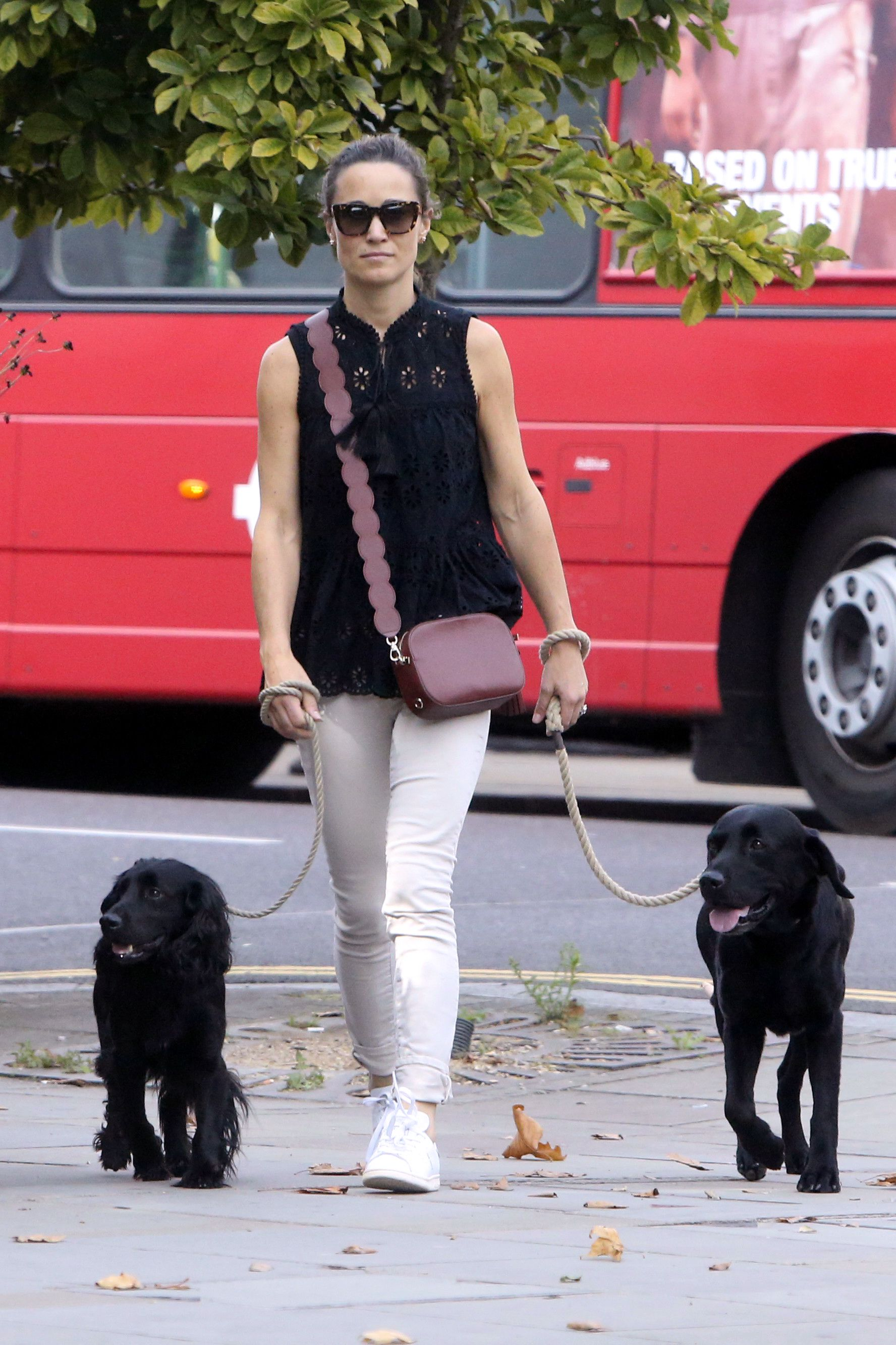 Pippa also owns the Pop and Suki camera bag in a wine color with a scallop strap. She styled the crossbody accessory with a black top and white jeans while out walking her dogs in London.