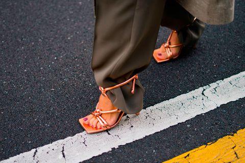 Orange, Footwear, Asphalt, Street fashion, Shoe, Human leg, Yellow, Road surface, Jeans, Leg,