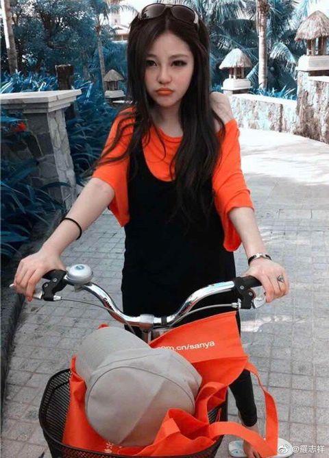 Product, Vehicle, Orange, Leg, Bicycle, Photography, Long hair, Sitting, Smile, Thigh,