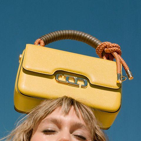 マーク ジェイコブスの黄色のザ ジェイ リンクを頭に載せたモデル