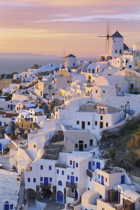 view of oia with traditional greek windmills, sunset, santorini, cyclades, mediterranean sea, greece