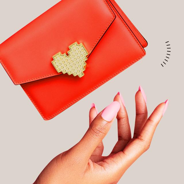 a hand throwing a handbag in the air