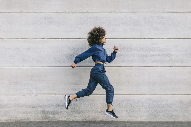 jonge vrouw springt in hardloophouding voor betonnen muur