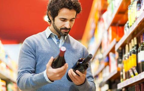man deciding what wine to purchase