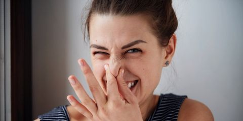 woman holding nose poop smell