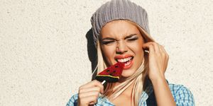 woman eating lollipop with tooth pain