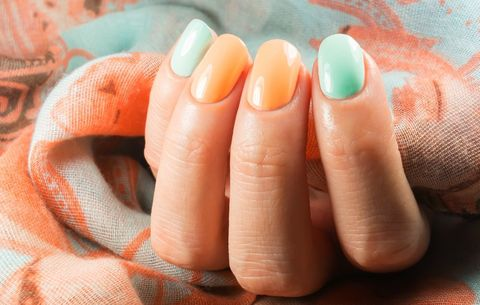 Fingernails Painted In Orange And Blue