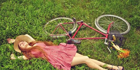 a woman laying in the grass next to her bike.