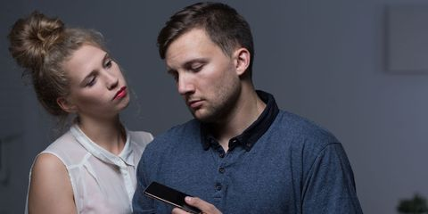 A man handing his phone to a woman