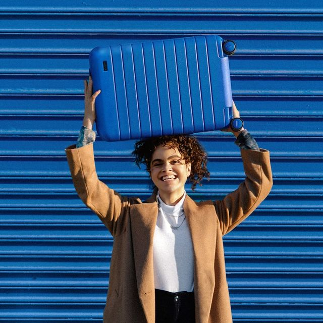 woman holding blue away luggage over head