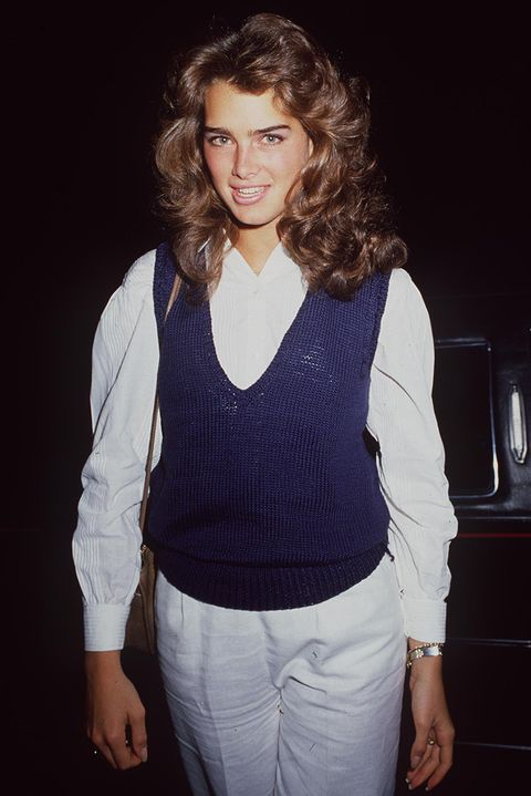 Brooke Shields wearing a white blouse and trousers, finished with a blue sweater vest over the top and voluminous hair.