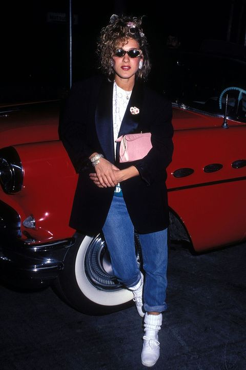 Sarah Jessica Parker in the 80s wearing mum jeans, a white top, black blazer and white trainers while leaning against a red car. The star finishes the outfit with a red lip, a messy up-do hair style and big earrings.