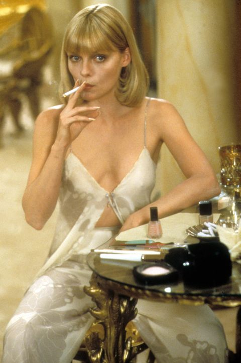 A film still from Scarface showing Michelle Pheiffer wearing ivory pyjama coordinates while smoking a cigarette in her boudoir.