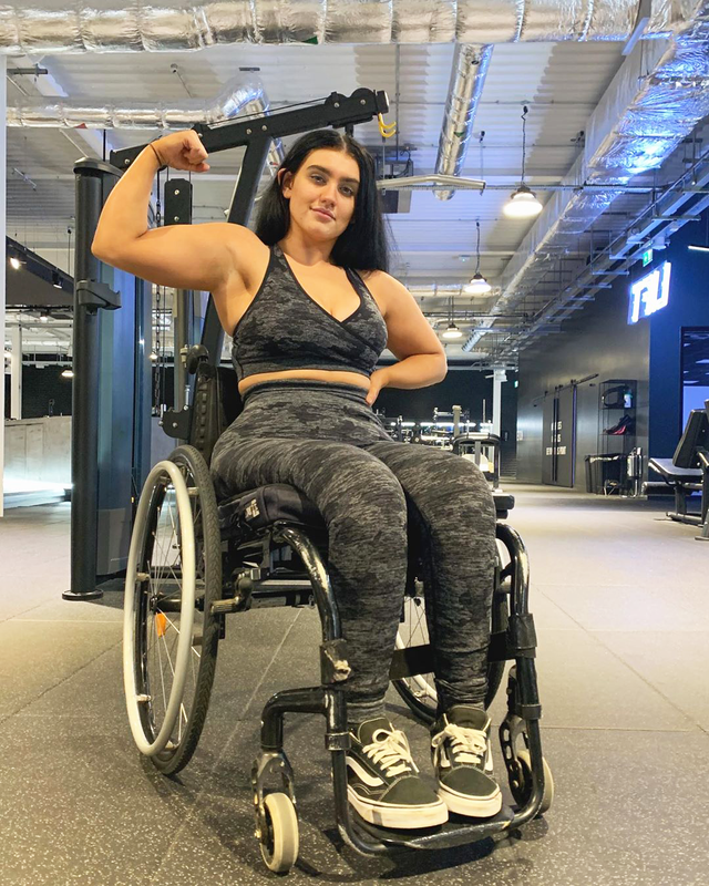 social media influencer sophie butler flexing muscles in wheelchair at the gym