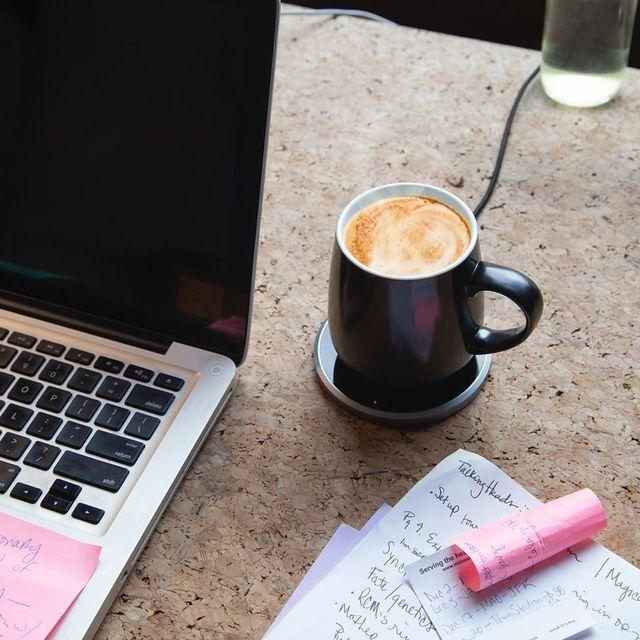 ceramic mug warmer next to laptop and notes