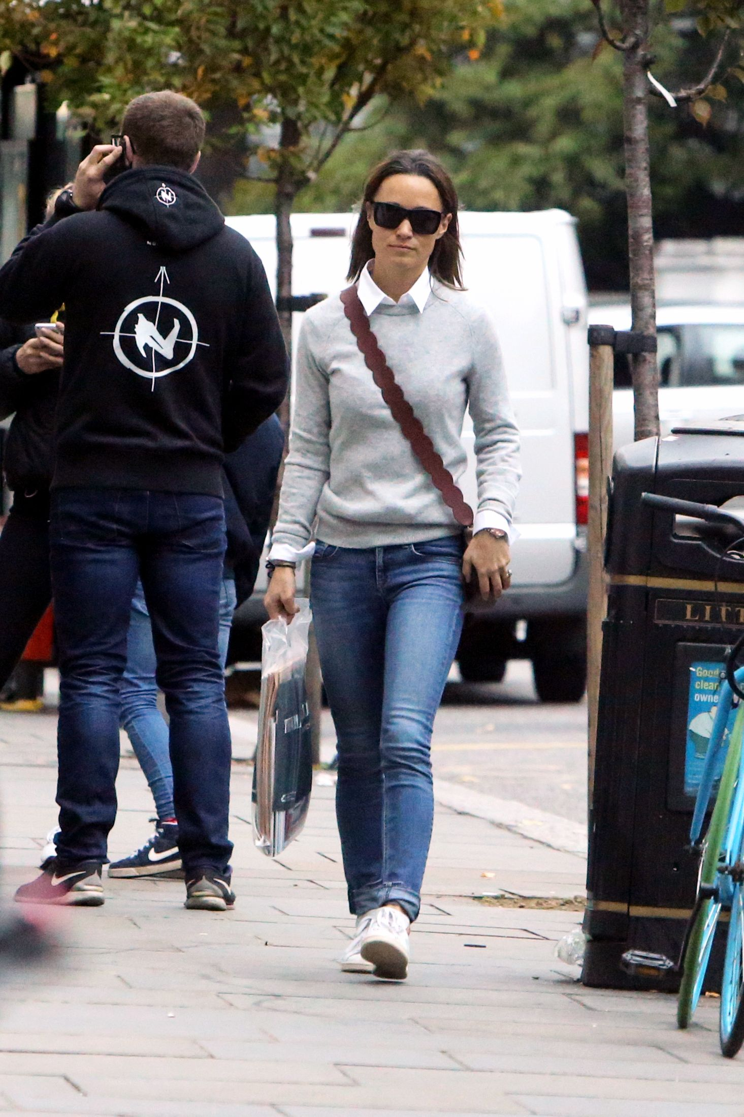 Pippa ran errands around London while wearing a gray sweater and white button down with blue jeans. Her Pop and Suki bag added a subtle hint of color to her casual outfit.