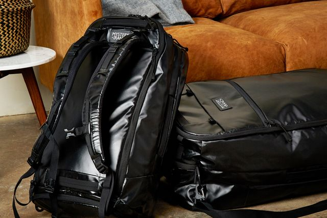two black duffel bags on the floor near a couch