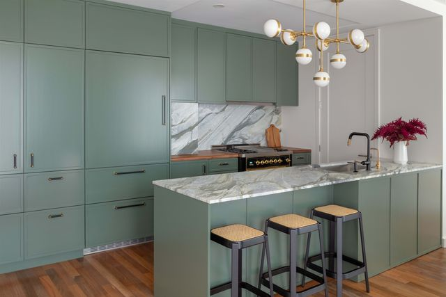 green kitchen, green cabinets, white ceiling light, marble countertops, marble back splash