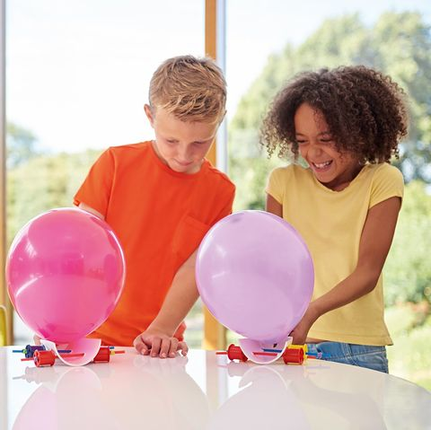 a girl and boy creating a balloon project inside