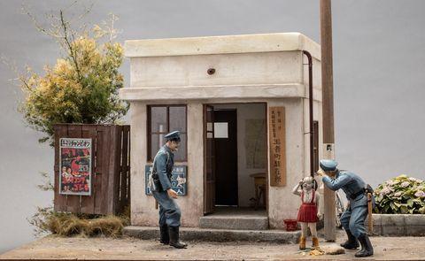 米白色的建築物前有藍色衣服的警察和紅色衣服的女孩