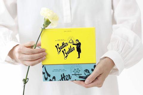一個人穿白色衣服拿著黃色和藍色的盒子