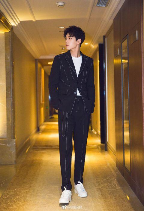 Clothing, Suit, Standing, Formal wear, Outerwear, Blazer, Fashion, Pantsuit, Street fashion, Trousers,