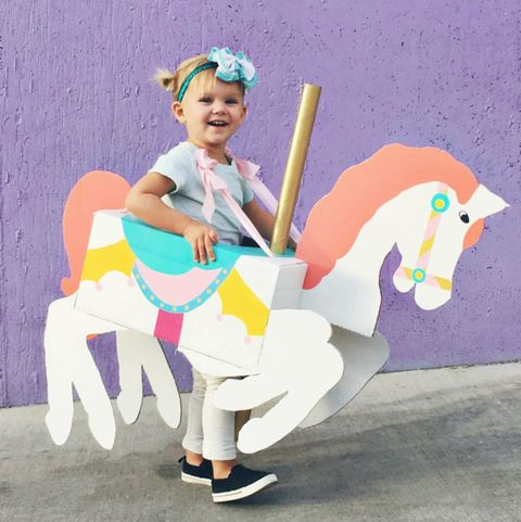 little girl with a box shaped and painted to look like a carousel horse around her
