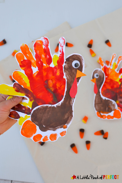hand holding a painted turkey craft made out of a kid's footprint for the body and a kid's hand print for the feathers with a googly eye there is another turkey and candy corn in the background