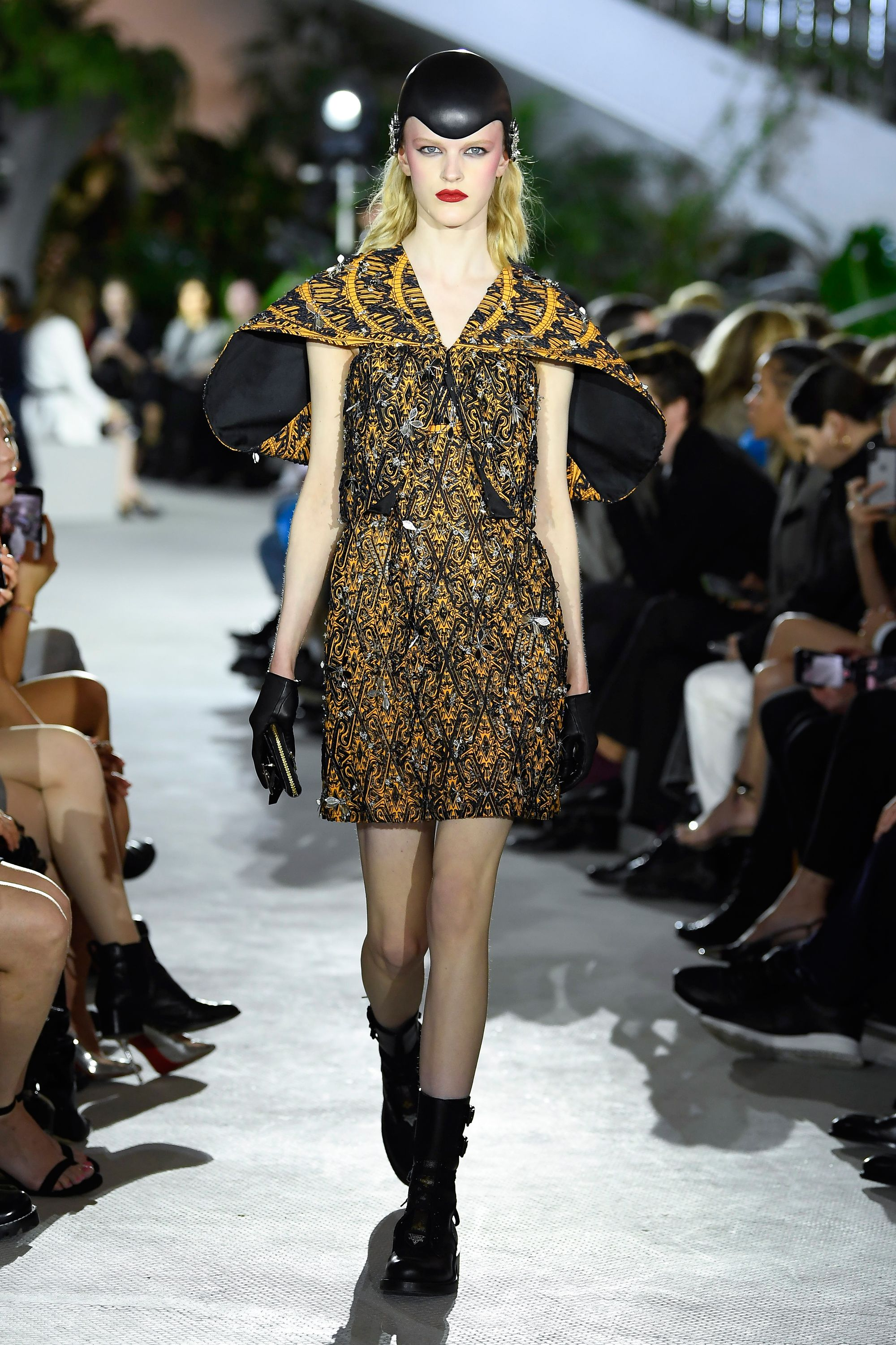 Aviator-style caps, dramatic shoulder pads, and elegant black gloves evoke travel, past and future at Nicolas Ghesquiere's 2020 Cruise Collection for Louis Vuitton.