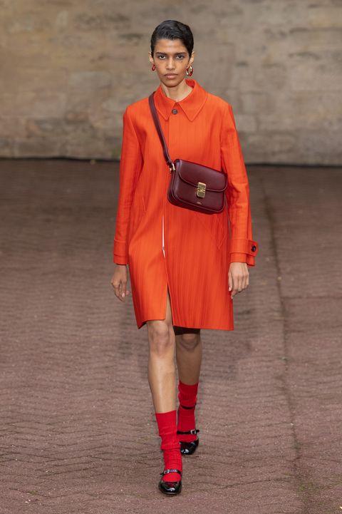 Fashion model, Fashion, Fashion show, Runway, Orange, Clothing, Red, Footwear, Street fashion, Shoulder,