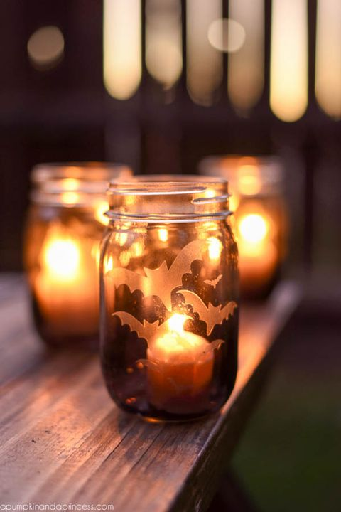 mason jar with etched glass look flying bats on it, and lighted candle inside, other ones blurry in the background