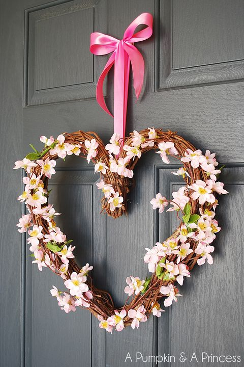 grapevine wreath in the shape of a heart with floral stems twisted around it hanging from a door from a pink satin bow