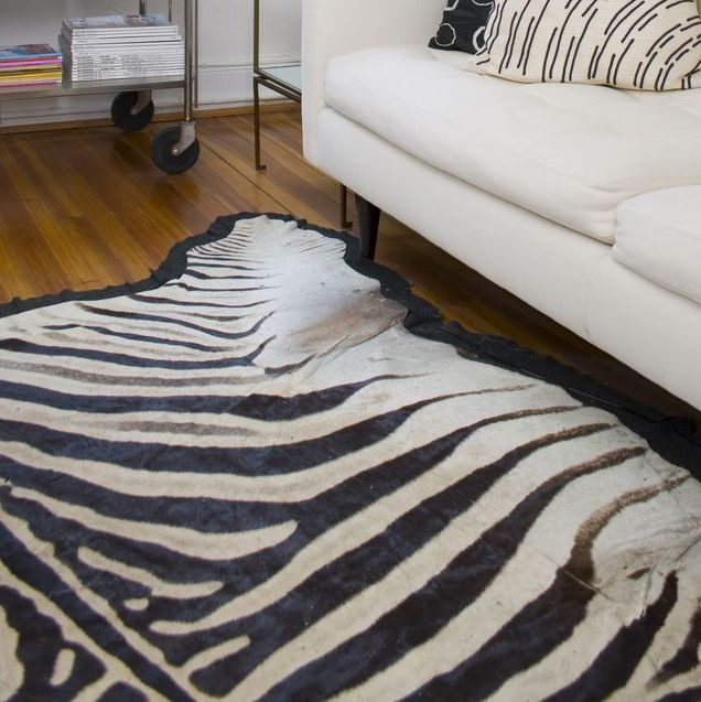 retro white home interior with midcentury couch, vintage barss floor lamp and antique zebra rug