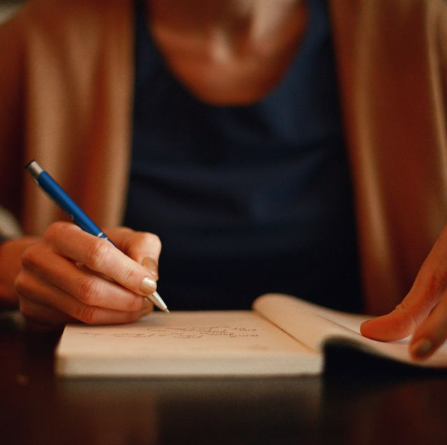 a woman writing in a notebook