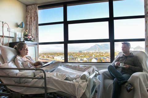 a young man spends time with his wife in hospital as she recovers from a caesarean section