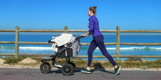 a young mother jogging on the beachfront pushing a stroller