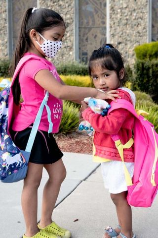 two girls wearing new backpacks