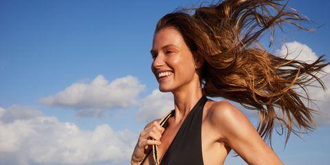 model op strand met lang haar, badpak en tas